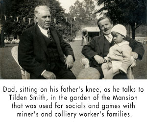 Dad, sitting on his father's knee, as he talks to Tilden Smith, in the garden of the Mansion that was used for socials and games with miner's and colliery worker's families.